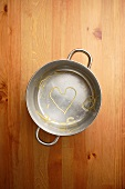 Heart shaped spaghetti in cooking pot on wooden table