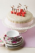 Cake decorated with butterflies shaped and marzipan, cup and saucer in foreground