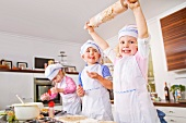Germany, Girls and boy baking cup cakes in kitchen