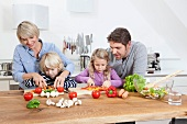 Germany, Bavaria, Munich, Family preparing food in kitchen