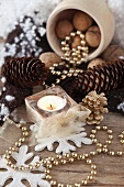 Christmas decorations with pine cones, nuts, string of peals and a tea light