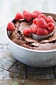 Chocolate-raspberry cake with fresh raspberries in a cake pan