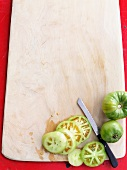 Green tomatoes, partly sliced, on a chopping board