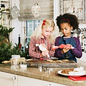 Two girls decorating Christmas biscuits