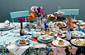 A plentiful array of cakes with a colourful floral display