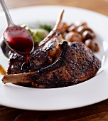 Spooning a Glaze Over Frenched Lamb Chops; In a White Bowl