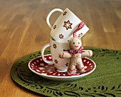 Two Christmas Mugs Stacked on a Saucer with a Small Stuffed Gingerbread Man