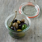 Assorted Olives in a Small Jar; Opened on a Wooden Surface