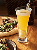 Pouring Beer into a Glass of Panache; Arugula Pizza