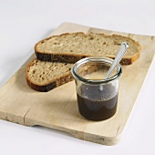 Sugar Beet Syrup with Slices of Bread on a Cutting Board