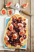 Tarte flambée with red onions, pancetta, goat's cheese and figs