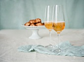 Two Glasses of Champagne with a Pedestal Dish of Macaroons in the Background