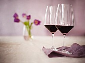 Two Glasses of Burgundy Wine With Purple Flowers in the Background