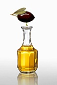 A black olive with an oil droplet over a carafe of olive oil