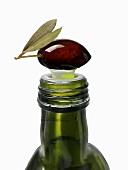 A black olive on top of an olive oil bottle