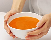 A woman's hands holding a bowl of cream of tomato soup