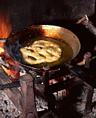 A fritter sizzling in olive oil