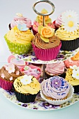 close up of a selction of iced purple, yellow and pink cup cakes decorated with icing flowers on a purple pansy flowered cake stand and a white background
