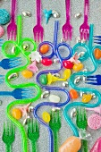 graphic overview of coloured plastic party forks and blue and purple curved drinking straws on a silver glittery background with sweets