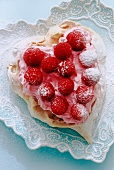 heart shaped meringue with cream and rasberries on heart shape plate