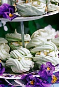 pistacio meringues on a cake stand with pansy flowers