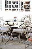 Schwarzer Metalltisch mit verspielten Metallstüheln auf der Terrasse eines Restaurants