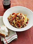 Fettuccine with bolognese sauce and a piece of bread