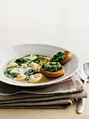 Clear broth with tortellini and spinach, served with pesto on toast