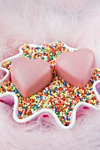 two romantic pink love heart shaped chocolates for valentine s day, in a pink spotted cake cover laying on coloured hundreds and thousand sweets with pale pink feathers
