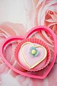 Rosa Cupcake mit Zuckerblume in einer Plastikausstechform