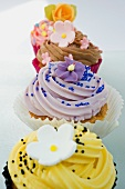 close up, selective focus of a row of coloured cup cakes, decorated with orange, pink and purple flowers on top