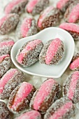 close up of pink marzipan stuffed dates with two laying in a white heart shaped ceramic dish