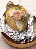 Foil-wrapped baked potato with prawns and sour cream