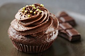 A Single Chocolate Cupcake with Chocolate Frosting and White Sprinkles