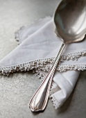 A sauce spoon on a lace-edged napkin