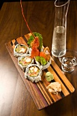 Lobster Sushi on a Wooden Platter; Pitcher and Glass of Sake