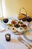 Viele verschiedene mediterrane Dips und Aufstriche auf einem Tisch mit Wein und Fladenbrot