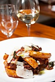 Rigatoni with Short Ribs and Shaved Parmesan Cheese; On a White Plate; Glass of White Wine in Background