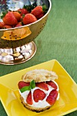 A plate of strawberry shortcake with cream and a stainless steel colander with fresh strawberries