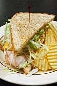 Turkey sandwich with cheese and salad and crisps