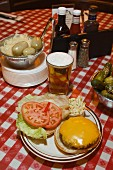 A cheeseburger, beer and pickled gherkins on a checked tablecloth