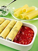 Canneloni with tomato sauce being prepared