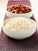 A bowl of rice and a bowl of chilli con carne
