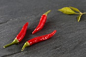 Three fresh red chilli peppers on a stone slab