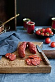 Cured sausage with paprika, on a chopping board