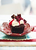 A Black Forest cherry cupcake with cherry compote and white chocolate cream topping