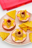 Sliced turnip topped with tortilla chips and aubergine caviar