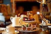Etagere mit Desserts, Kuchen und Konfekt zwischen Kaffeegeschirr