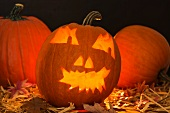 Lit Halloween lanterns on straw