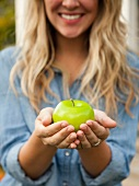 A blonde woman holding a green apple